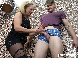 Maw gives a blowjob and tugjob to young guy in the sauna
